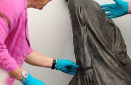 met handschoen wordt een kunstwerk aangeraakt