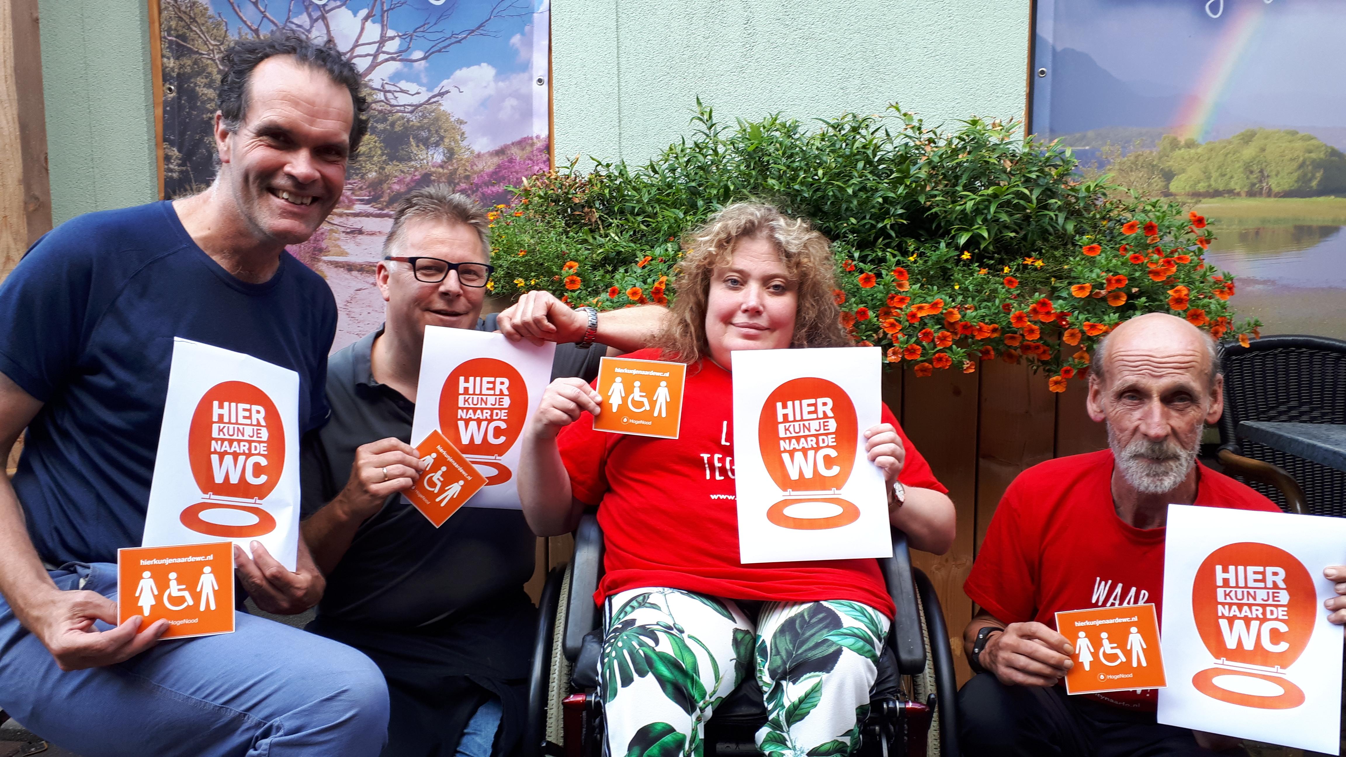 Drie mannen en een vrouw in een rolstoel tonen een sticker en een flyer met opschrift 'Hier kan je naar de WC.'