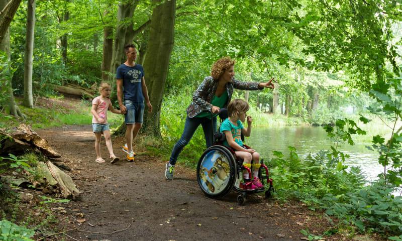 vier mensen wandelen over een goed begaan pad, een meisje in een rolstoel