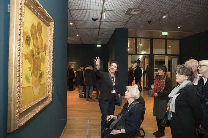 Groep mensen onder wie een mevrouw in een rolstroel bekijken een zonnebbloemenschilderij van Van Gogh