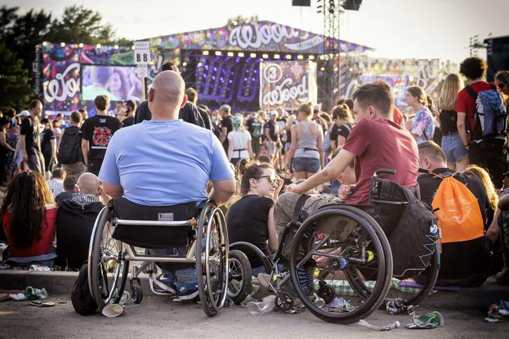 Twee mannen in rolstoel kijken naar een concert