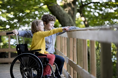 2 kinderen aan het kijken waarvan 1 in een rolstoel