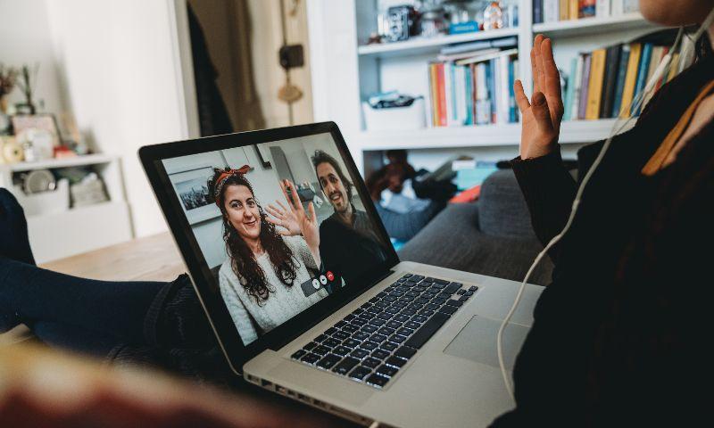 Jonge mensen zwaaien lachend via videobellen naar elkaar