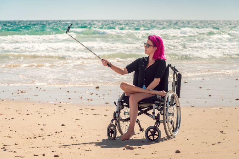 jonge vrouw in rolstoel op strand maakt selfie langs de branding