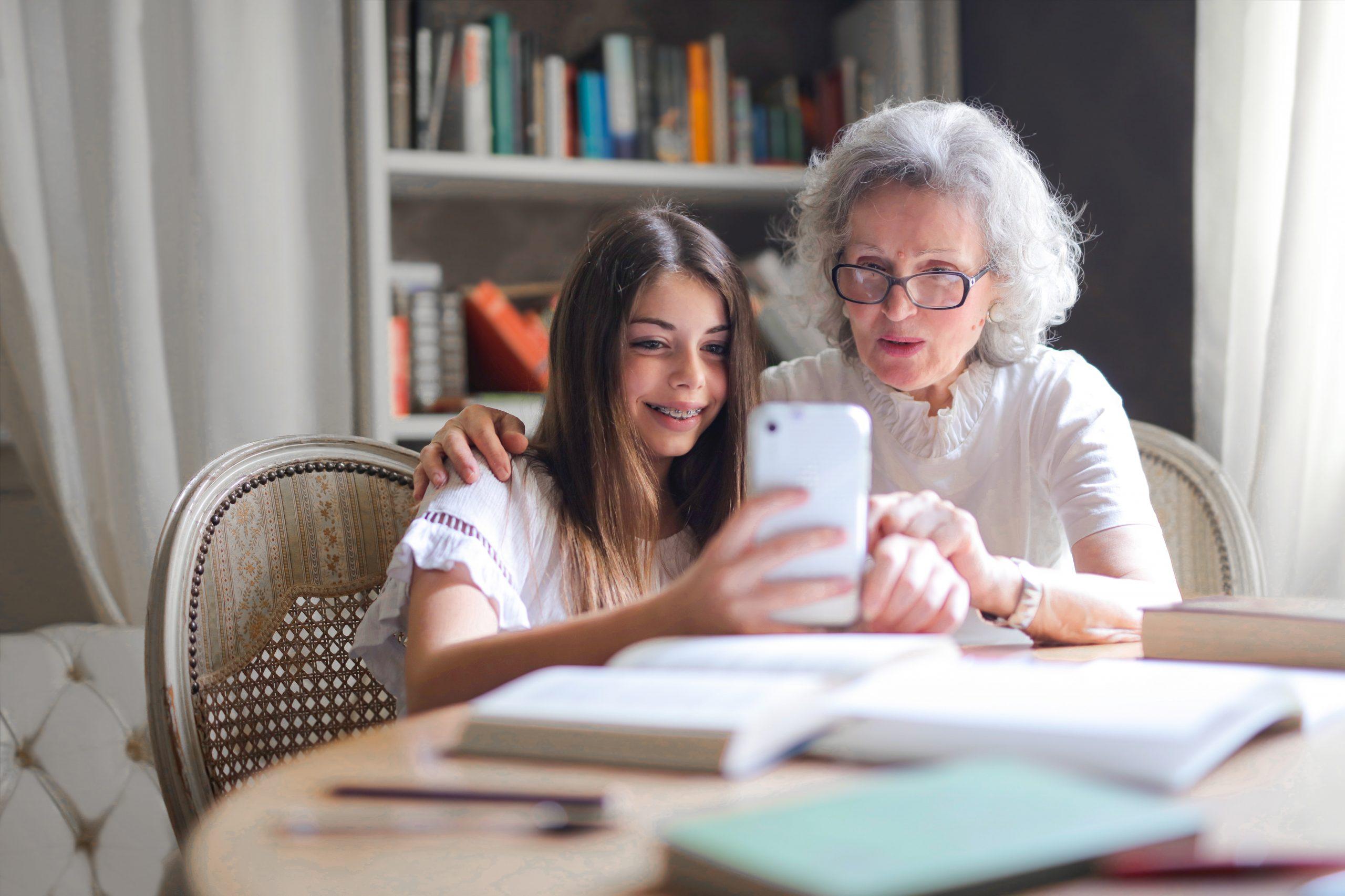 Oudere vrouw met kleindochter kijken samen op telefoon