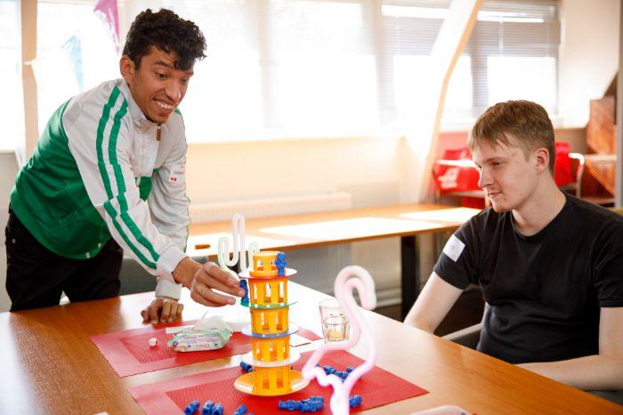 Twee jongeren spelen aan tafel een gezelschapsspel