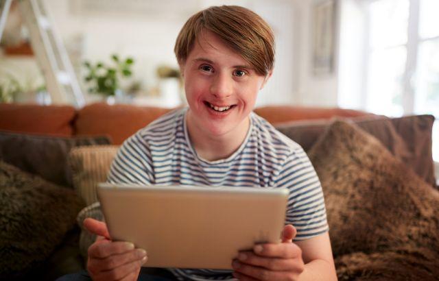 jongen met licht verstandelijke beperking met laptop, hij kijkt blij