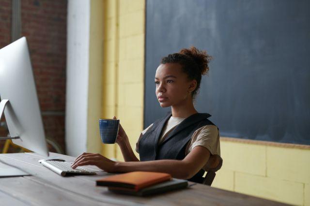 jonge vrouw achter computerscherm kijkt aandachtig