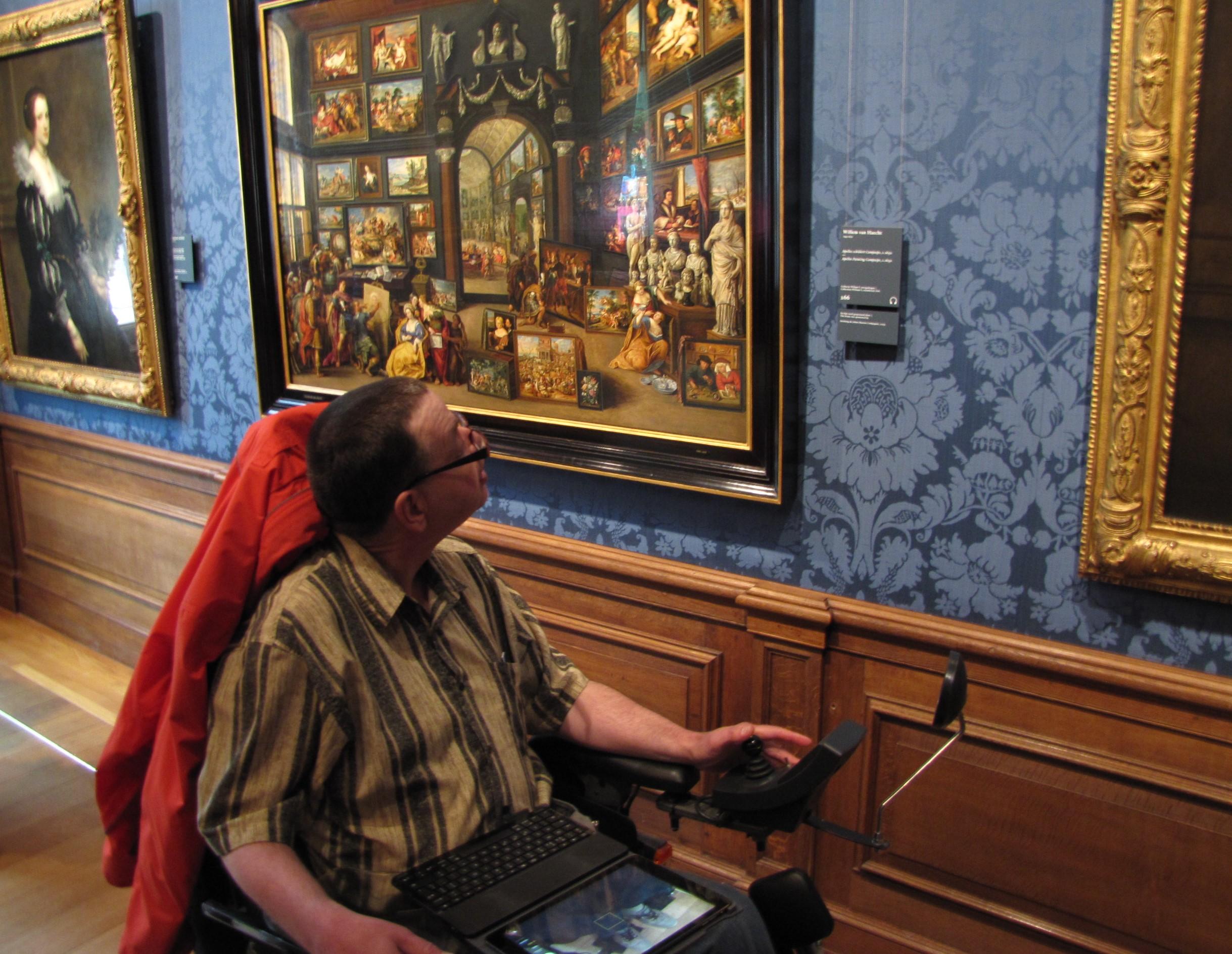 Een man in rolstoel rijdt langs een schilderij in het mauritshuis