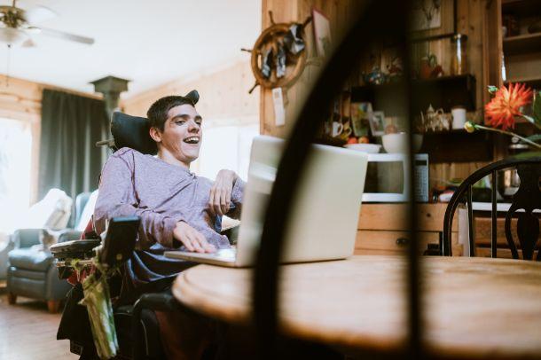 jongeman in elektrische rolstoel lachend in huiskamer voor een grote laptop