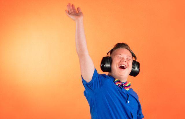 jongen met downsyndroom danst blij met koptelefoon op