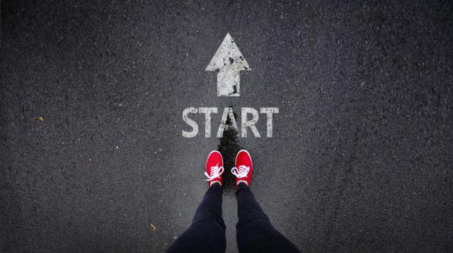 twee voeten in rode gympen bij een startpunt op een weg